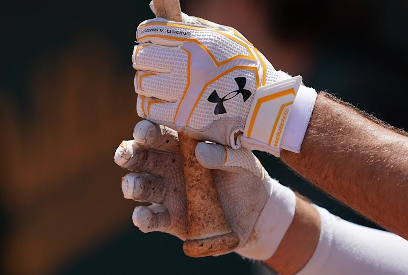 OAKLAND, CA - JULY 17: Matt Olson #28 of the Oakland Athletics stand in the dugout wearing Under Armour batting gloves while holding onto his bat against the Seattle Mariners in the bottom of the fourth inning at Ring Central Coliseum on July 17, 2019 in Oakland, California. (Photo by Thearon W. Henderson/Getty Images)