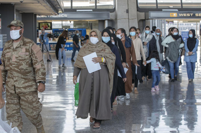 Families evacuated from Kabul, Afghanistan, walk through the terminal to board a bus after they arrived at Washington Dulles International Airport, in Chantilly, Va., on Saturday, Aug. 28, 2021. (AP Photo/Gemunu Amarasinghe)