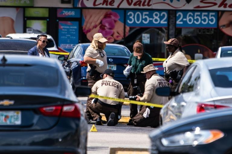 Miami Dade police officers collect evidence from the parking lot outside the hall that was the scene of the shooting