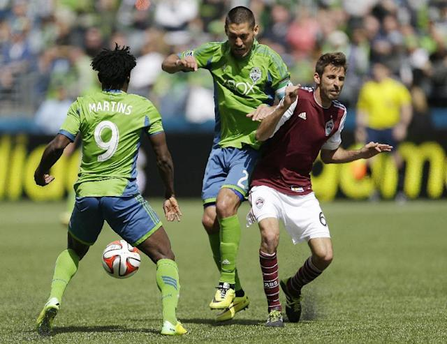 Seattle Sounders' Clint Dempsey, center, and Obafemi Martins, left, battle for the ball with Colorado Rapids' Jose Mari, right, Saturday, April 26, 2014, in the second half of an MLS soccer match in Seattle. (AP Photo/Ted S. Warren)