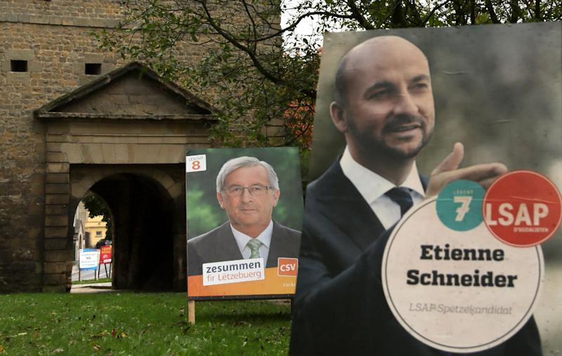 Campaign boards for Socialist Party candidate Etienne Schneider, right, and incumbent prime minister Jean-Claude Juncker, center, are placed along the side of the street in Luxembourg on Saturday, Oct. 19, 2013. General elections will be held in Luxembourg on Sunday, Oct. 20, 2013. Early elections were called for after Prime Minister Jean-Claude Juncker's Socialist coalition partner withdrew its support in July 2013 and insisted he should take political responsibility for an old secret service scandal which centered on snooping on local politicians. (AP Photo/Virginia Mayo)