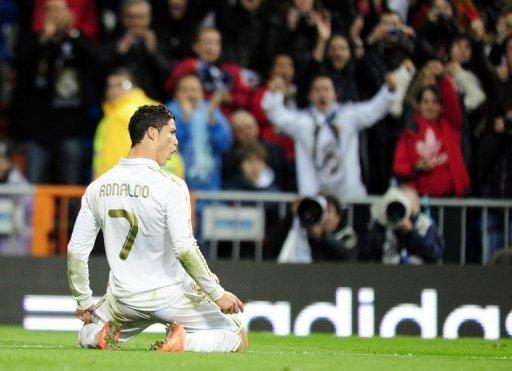 Real Madrid's forward Cristiano Ronaldo celebrates after scoring against Sporting Gijon at the Santiago Barnabeu stadium in Madrid. Ronaldo set a new La Liga scoring record and Real Madrid equalled the highest ever goal tally in a season as they came from behind to beat Sporting Gijon 3-1 and open a seven-point lead over Barcelona