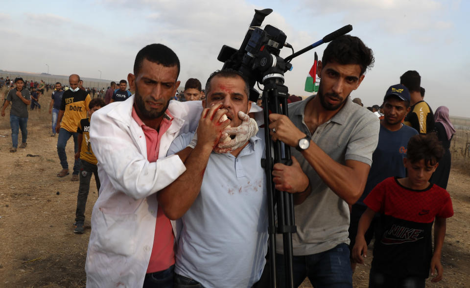 Medics and protestors evacuate a wounded of cameraman of Asem Shehada, from the fence of Gaza Strip border with Israel, during a protest marking the anniversary of a 1969 arson attack at Jerusalem's Al-Aqsa mosque by an Australian tourist later found to be mentally ill, east of Gaza City, Saturday, Aug. 21, 2021. (AP Photo/Adel Hana)