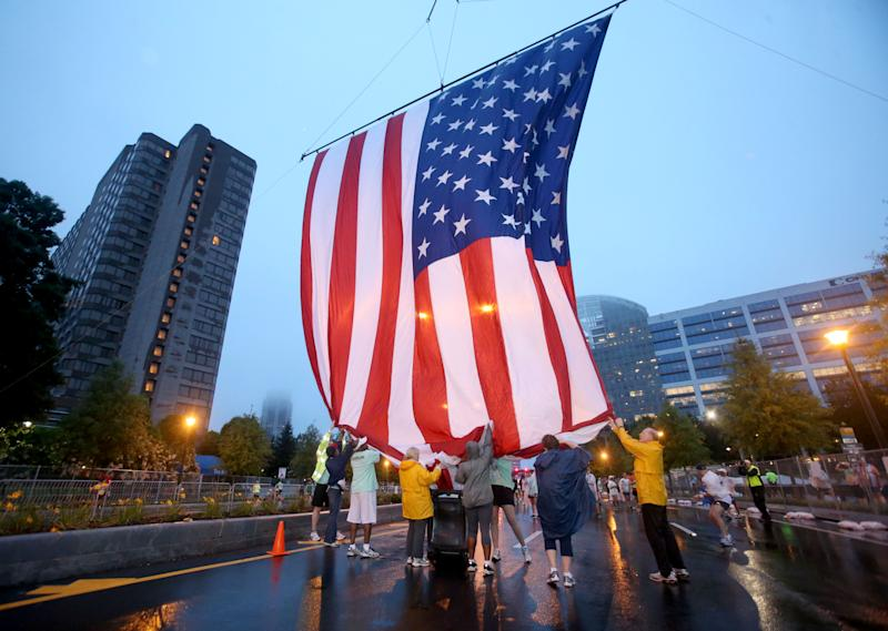 Volunteers hoist up the U.S. flag at the starting line before the start of the 44th running of the AJC Peachtree Road Race at Lenox Square Thursday morning in Atlanta, Ga., July 4, 2013. The 10K race is a Fourth of July tradition in Atlanta that's billed as the largest road race in the U.S. (AP Photo/Atlanta Journal-Constitution,Jason Getz ) MARIETTA DAILY OUT; GWINNETT DAILY POST OUT; LOCAL TV OUT; WXIA-TV OUT; WGCL-TV OUT