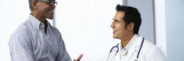 Doctor In Surgery With Male Patient Using Digital Tablet Smiling To Each Other.