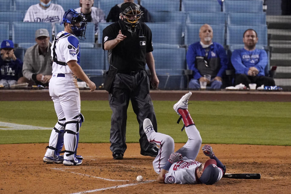 Washington Nationals' Yadiel Hernandez, right, lays on the ground after being hit by a pitch as Los Angeles Dodgers catcher Will Smith, left, watches and home plate umpire Brian Gorman gestures during the sixth inning of a baseball game Saturday, April 10, 2021, in Los Angeles. (AP Photo/Mark J. Terrill)