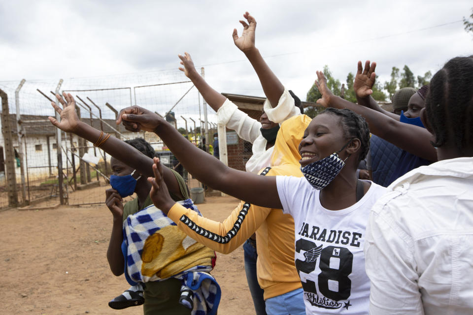 Female prsioners wave goodbye to their fellow inmates following their release from Chikurubi prison on the outskirts of Harare, Saturday, April 17, 2021. Zimbabwe began the release of about 3,000 prisoners under a presidential amnesty aimed at easing congestion and minimizing the threat of COVID-19 across the country's overcrowded jails. (AP Photo/Tsvangirayi Mukwazhi)