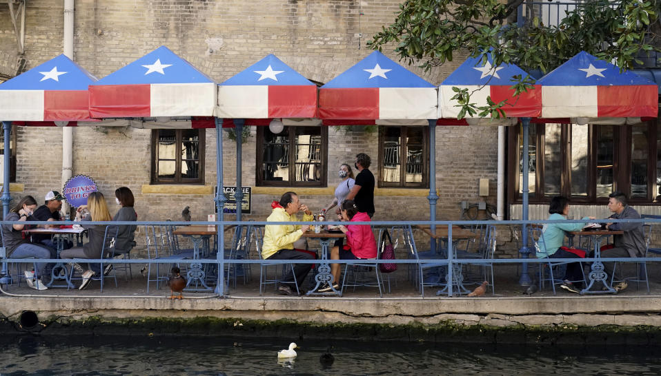Diners eat at a restaurant on the River Walk, Wednesday, March 3, 2021, in San Antonio. Gov. Greg Abbott says Texas is lifting a mask mandate and lifting business capacity limits next week. (AP Photo/Eric Gay)