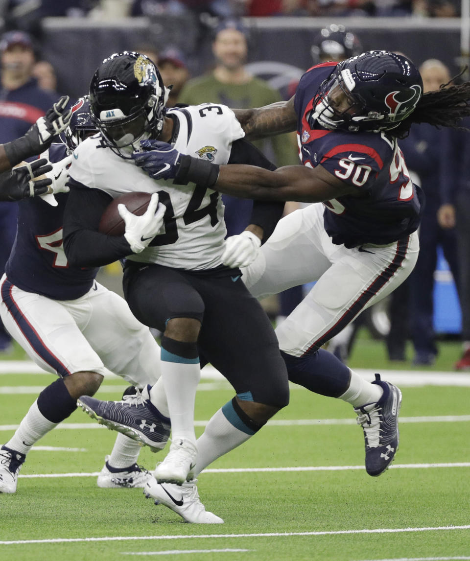 Jacksonville Jaguars running back Carlos Hyde (34) is stopped by Houston Texans outside linebacker Jadeveon Clowney (90) during the first half of an NFL football game, Sunday, Dec. 30, 2018, in Houston. (AP Photo/David J. Phillip)