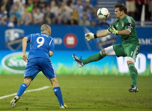 Chivas USA's goalkeeper Dan Kennedy, right, makes a save against Montreal Impact's Marco Di Vaio during second half MLS soccer action in Montreal, Sunday, July 7, 2013. (AP Photo/The Canadian Press, Graham Hughes)