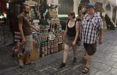 Tourists look at Tunisian selling Argan Oil during the holy month of Ramadan in downtown Tunisia