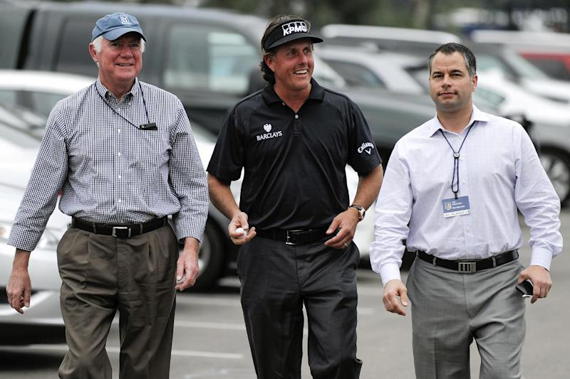 Phil Mickelson, center, walks with his spokesman T.R. Reinman, left, and PGA official Joel Schuchmann, right, as he arrives at a news conference held after his round in the pro-am at the Farmers Insurance Open golf tournament at Torrey Pines, Wednesday, Jan 23, 2013, in San Diego. (AP Photo/Denis Poroy)