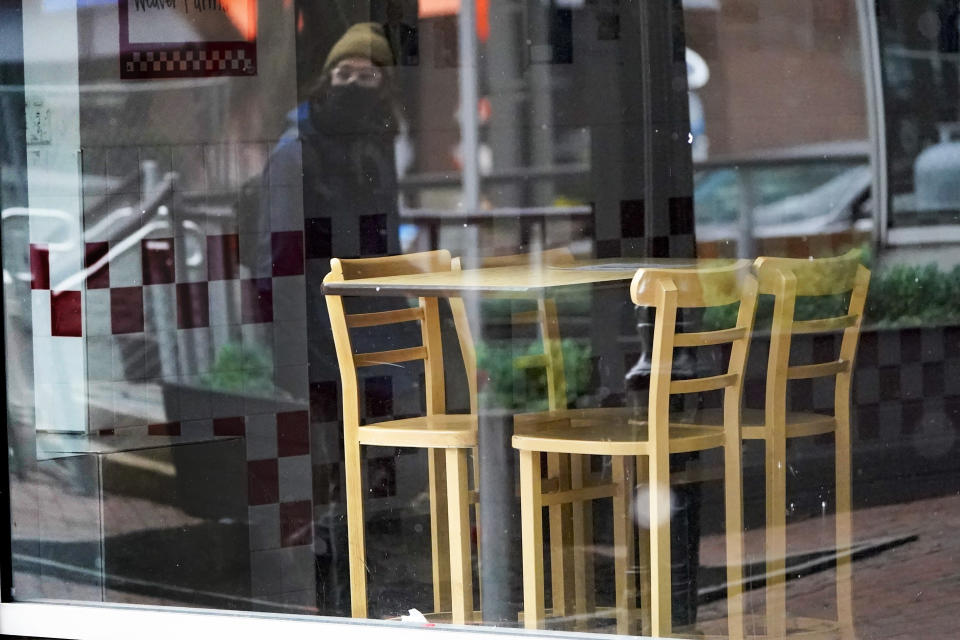 FILE - In this Jan. 17, 2021, file photo, a passerby wearing a protective mask is reflected in the window of an empty restaurant near Market Square in downtown Pittsburgh. Irritated by the sweeping use of executive orders during the COVID-19 crisis, state lawmakers around the U.S. are moving to curb the authority of governors and top health officials to impose emergency restrictions such as mask rules and business shutdowns. (AP Photo/Keith Srakocic, File)