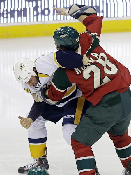 Minnesota Wild's Zenon Konopka, right, attempts to get the upper hand in a fight with Nashville Predators' Richard Clune in the first period of an NHL hockey game, Tuesday, Oct. 22, 2013, in St. Paul, Minn. Both received five-minute fighting penalties. (AP Photo/Jim Mone)
