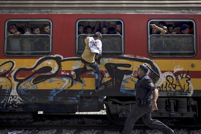 <p>A policeman tries to stop a migrant from boarding a train through a window at Gevgelija train station in Macedonia, close to the border with Greece, Aug. 15, 2015. <i>(Stoyan Nenov/Reuters)</i></p>