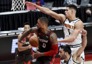 Portland Trail Blazers guard Damian Lillard, center, passes the ball behind his back to guard CJ McCollum, left, as Denver Nuggets forward Michael Porter Jr., right, defends during the first half of an NBA basketball game in Portland, Ore., Sunday, May 16, 2021. (AP Photo/Steve Dykes)