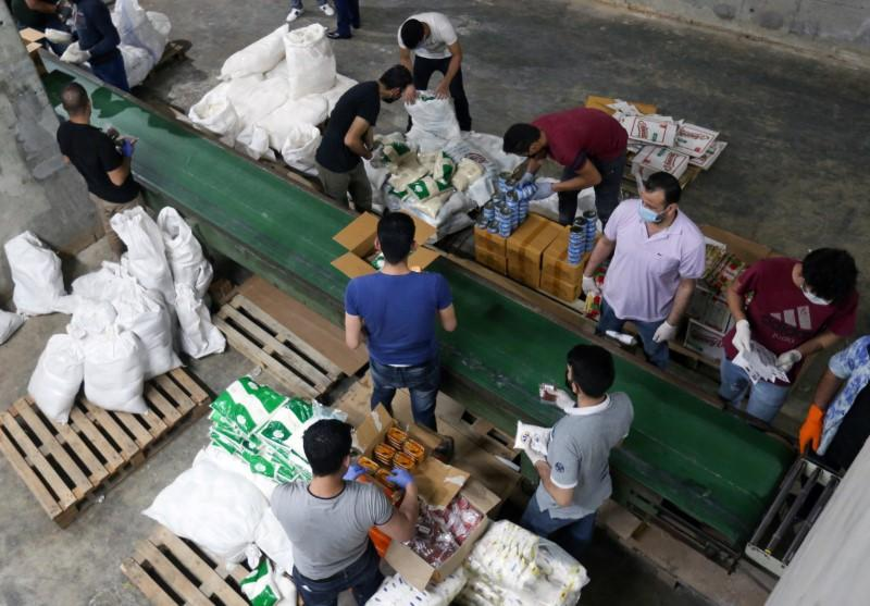 Volunteers wearing protective masks and gloves sort boxes with food for distribution to people in need, in Beirut