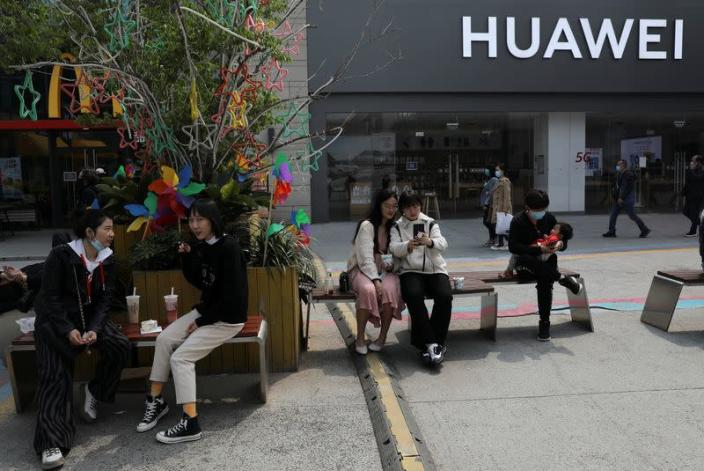 People rest in front of a Huawei store at a shopping complex in Beijin