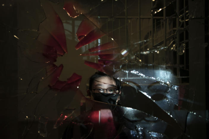 A 14-year-old protester who identified herself as K.C., poses for a portrait as a projector displays a photograph, previously taken during the unrest, over her at a protest in Hong Kong. For many protesters, identity is entwined with surveillance. Their signature masks, umbrellas and top-to-bottom black outfits shield them not only from physical threats like the riot police's tear gas and rubber bullets, but also from the invisible dangers of government identification and tracking. (Photo: Felipe Dana/AP)