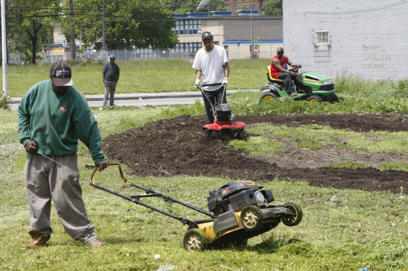 FILE- In this Thursday, May 20, 2010 photo, work crews clear out an empty lot in Detroit. Kraft Foods Inc.'s Triscuit brand and a nonprofit organization that works to establish working farms on unused land are announcing plans to create three community gardens at low-income housing developments in Chicago and two in Los Angeles. The plans for the gardens will be announced Tuesday, April 12, 2011 in New York hosted by Triscuit and Urban Farming. (AP Photo/Carlos Osorio, FILE)