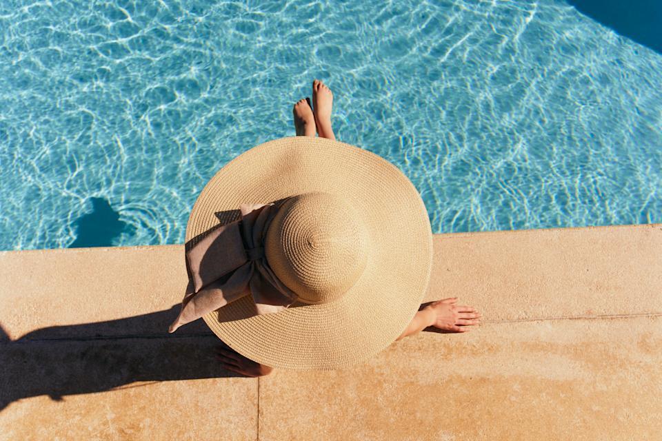 Woman in hat lies near the pool, bright sun
