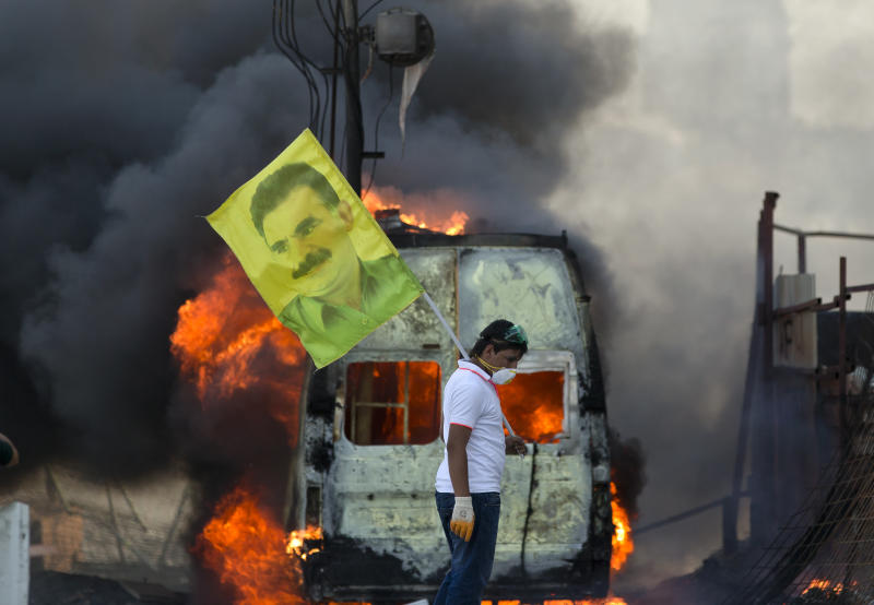 A protester holds  a flag depicting  jailed Kurdish rebel leader Abdullah Ocalan as a van burns during clashes at the Taksim Square in Istanbul Tuesday, June 11, 2013.Hundreds of riot police overran improvised barricades at Istanbul's Taksim Square on Tuesday, firing tear gas, rubber bullets and water cannons in running battles with protesters who have been occupying the area for more than a week. (AP Photo/Vadim Ghirda)
