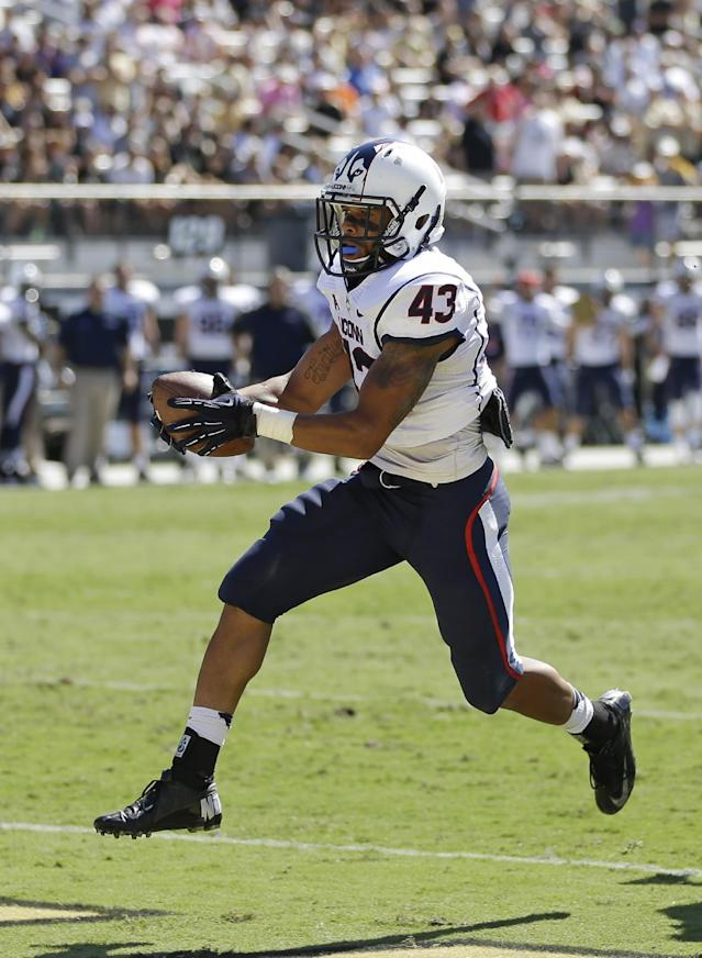 Connecticut running back Lyle McCombs (43) runs for a 9-yard touchdown against Central Florida during the first half of an NCAA college football game in Orlando, Fla., Saturday, Oct. 26, 2013.(AP Photo/John Raoux)