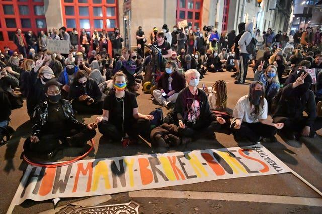 After marching through the city centre people staged a sit in outside Bridewell police station (Ben Birchall/PA).