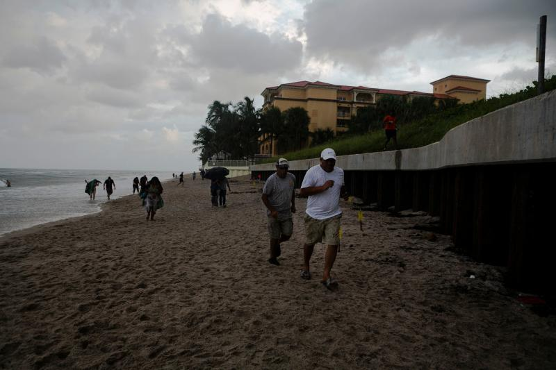 People run from the rain in Lantana Beach, Florida (Picture: Getty)