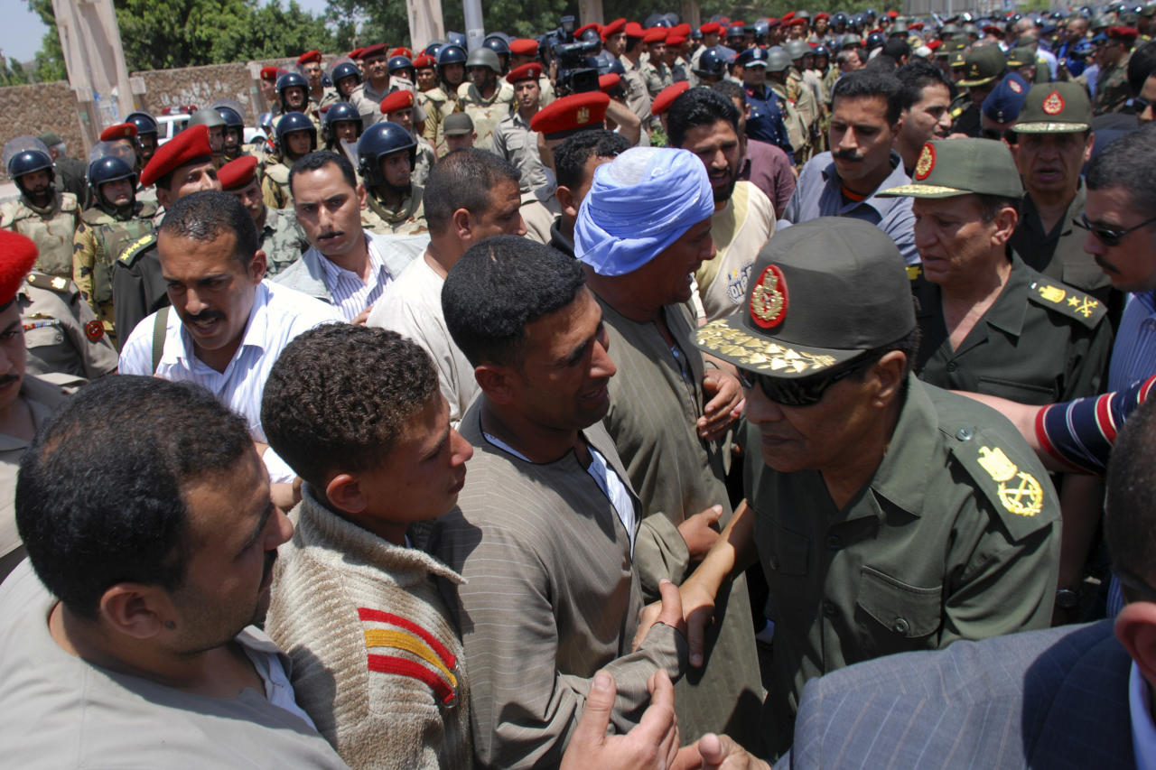 Field Marshal Hussein Tantawi, right, the head of Egypt's ruling Supreme Council of the Armed Forces (SCAF), greets mourners at a military funeral for Cpl. Samir Anwar Ismail, a commando killed in clashes with protesters in Cairo, Egypt, Saturday, May 5, 2012. Lawyers say authorities have detained over 300 Egyptian protesters including 18 women following clashes outside the country's Defense Ministry, accused of attacking troops and disrupting public order.(AP Photo)