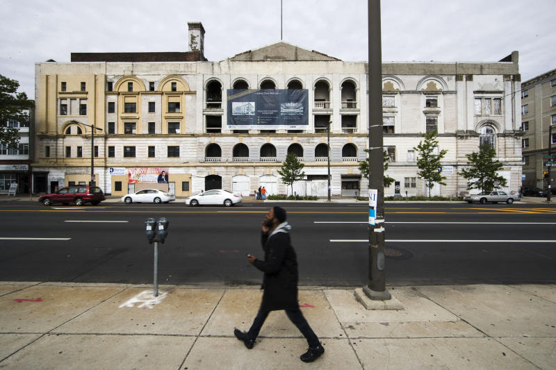 A man walks past the former Metropolitan Opera House in Philadelphia, Thursday, May 4, 2017. The glorious old opera house that takes up a full city block in Philadelphia will reopen as a live music venue. The Philadelphia Inquirer reports that developer Eric Blumenfeld has entered an agreement with Live Nation to revive the Metropolitan Opera House for $45 million. (AP Photo/Matt Rourke)