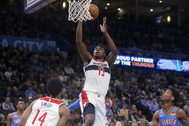 Washington Wizards center Thomas Bryant (13) goes up for a dunk as teammate Ish Smith (14) and Oklahoma City Thunder's Shai Gilgeous-Alexander, right, watch during the second quarter of an NBA basketball game Friday, Oct. 25, 2019, in Oklahoma City. (AP Photo/Sue Ogrocki)