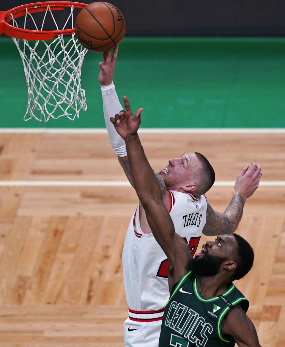 Chicago Bulls center Daniel Theis, left, tries to tip in a rebound against Boston Celtics guard Jaylen Brown, right, during the first half of an NBA basketball game, Monday, April 19, 2021, in Boston. (AP Photo/Charles Krupa)