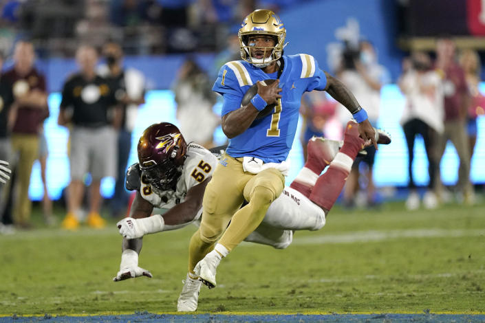 UCLA quarterback Dorian Thompson-Robinson, right, avoids a tackle by Arizona State defensive lineman Omarr Norman-Lott as he runs the ball during the second half of an NCAA college football game Saturday, Oct. 2, 2021, in Pasadena, Calif. Arizona State won 42-23. (AP Photo/Mark J. Terrill)