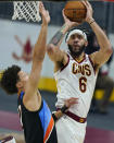 Cleveland Cavaliers' JaVale McGee, right, shoots over Oklahoma City Thunder's Isaiah Roby during the first half of an NBA basketball game Sunday, Feb. 21, 2021, in Cleveland. (AP Photo/Tony Dejak)