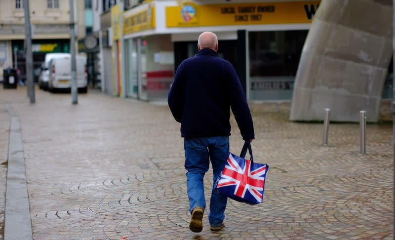 FILE PHOTO: A man carries a Union Jack themed shopping bag as he walks along an empty shopping street in Blackpool