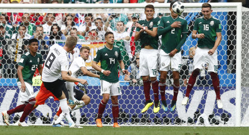 Germany's Toni Kroos, left, kicks a free kick during the group F match between Germany and Mexico at the 2018 soccer World Cup in the Luzhniki Stadium in Moscow, Russia, Sunday, June 17, 2018. (AP Photo/Matthias Schrader)