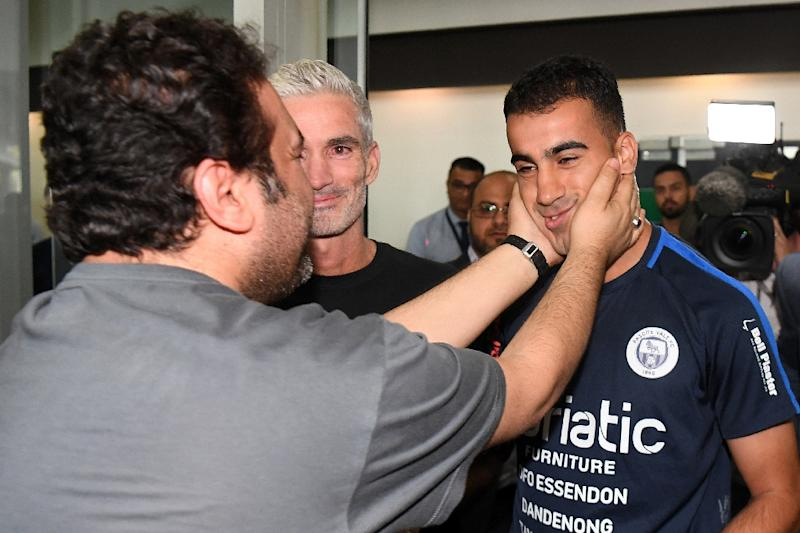 Hakeem al-Araibi (R) was greeted by a crowd of supporters including former Australian football captain Craig Foster (C) who led a campaign for his release (AFP Photo/WILLIAM WEST)