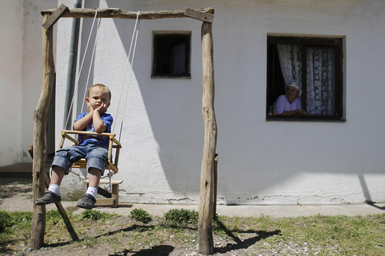 Bosnian Muslim Alija Avdic, aged 2, plays on a swing as his grandmother Rahima Avdic watches from the window of their shelter at the collective center for refugees near the northern Bosnian town of Zivinice, 130 kms north of Sarajevo, Monday, June 20, 2011, where the Avdic family settled after being displaced from their home in eastern Bosnia in 1995, Many refugees and internal displaced persons war still live in primitive shelters waiting to return to their destroyed pre-war homes, 16 years after the 1992-95 Bosnian war. On World Refugee Day, which is marked in Bosnia today, a total of 43.7 million displaced people have been registered in the world, 15.4 million of whom are refugees.(AP Photo/Amel Emric)