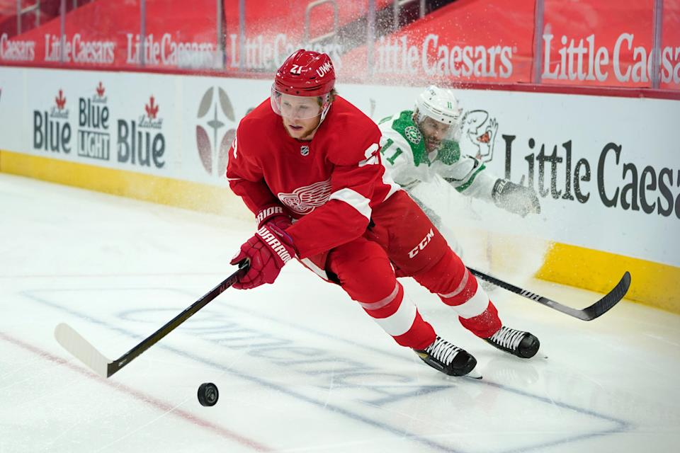 Detroit Red Wings defenseman Dennis Cholowski (21) protects the puck from Dallas Stars center Andrew Cogliano (11) in the first period of an NHL hockey game Thursday, April 22, 2021, in Detroit.