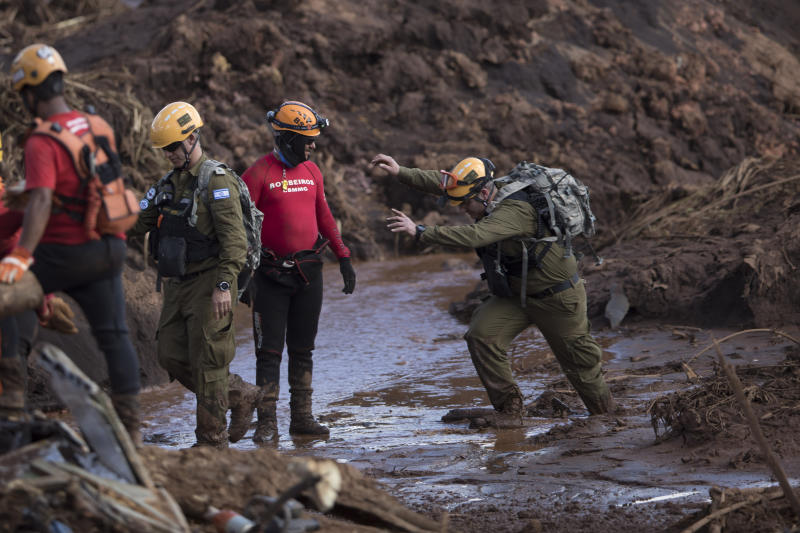 An Israeli rescue specialist, right, arrives at a site where a body was found inside a vehicle stuck in the mud, days after a dam collapse in Brumadinho, Brazil, Monday, Jan. 28, 2019. Firefighters on Monday carefully moved over treacherous mud, sometimes walking, sometimes crawling, in search of survivors or bodies four days after a dam collapse that buried mine buildings and surrounding neighborhoods with iron ore waste. (AP Photo/Leo Correa)