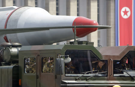 North Korean soldiers salute in a military vehicle carrying a missile during a parade in Pyongyang
