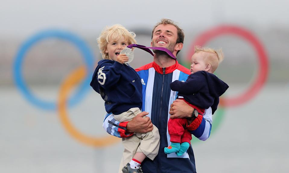 WEYMOUTH, ENGLAND - AUGUST 07: Silver medallist Nick Dempsey of Great Britain celebrates his children Thomas-Flynn (L) and Oscar (R) following the Men's RS:X Sailing on Day 11 of the London 2012 Olympic Games at the Weymouth & Portland Venue at Weymouth Harbour on August 7, 2012 in Weymouth, England. (Photo by Clive Mason/Getty Images)