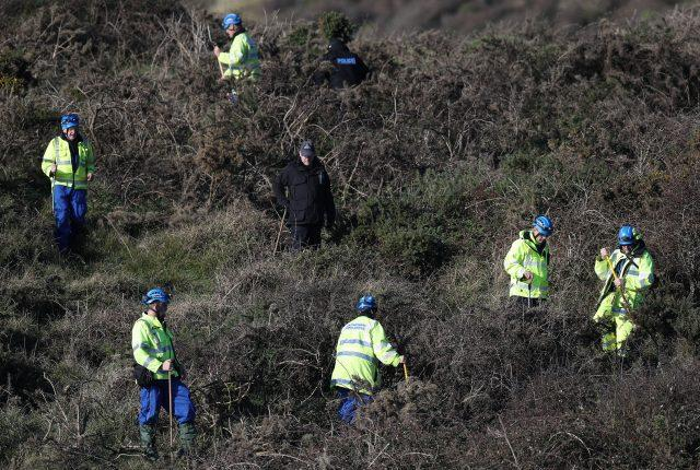 Police perform a fingertip search in the open space above the coast near to Swanage