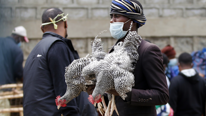 A poultry seller holding two birds in Addis Ababa, Ethiopia - Saturday 1 May 2021