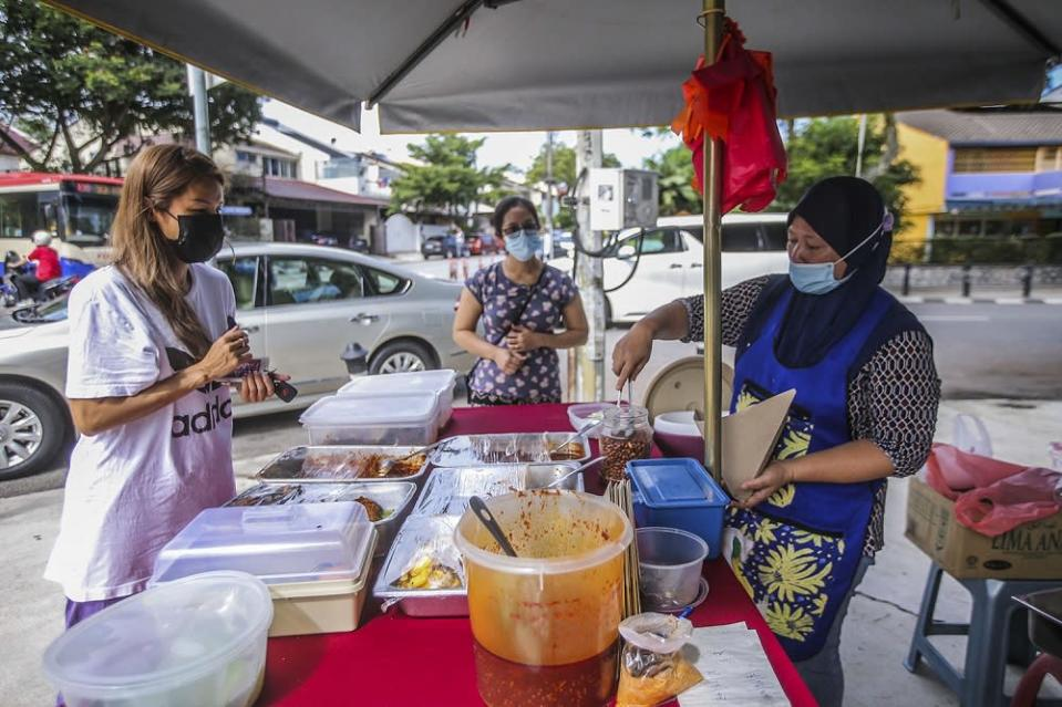 Nur Atikah Abdullah (right) serves customers at her nasi lemak stall along Jalan Telawi, Bangsar October 27, 2020. — Picture by Hari Anggara.