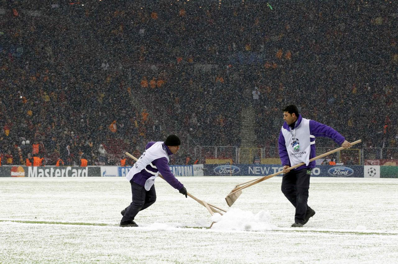 Workers rush to clean the snow from the pitch after the Champions League soccer match between Galatasaray and Juventus was paused for 20 minutes due heavy snowfall in Istanbul December 10, 2013. REUTERS/Osman Orsal (TURKEY - Tags: SPORT SOCCER)