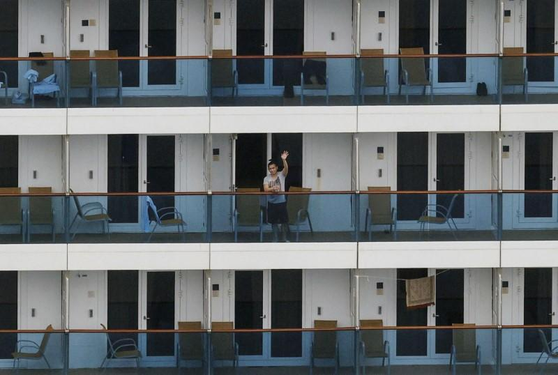 A crew member waves his hand on the balcony of Italian cruise ship Costa Atlantica, which has crew members confirmed with cases of the coronavirus disease (COVID-19) infection, in Nagasaki