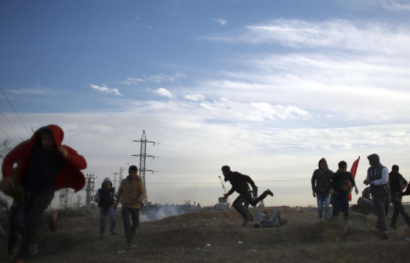Palestinian protesters run for cover during clashes on the Israeli border with Gaza, Monday, Dec. 11, 2017. (AP Photo/ Khalil Hamra)