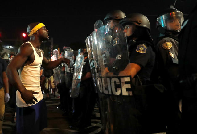 <p>A man yells at police in riot gear just before a crowd turned violent Saturday, Sept. 16, 2017, in University City, Mo. (Photo: Jeff Roberson/AP) </p>
